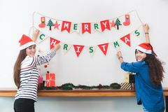 Two Asia woman decorate Christmas party banner flag at house wal. Two Asia women decorate Christmas party banner flag at house wall,Holiday celebration concept stock photos