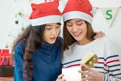 Two asia woman surprise when open gold gift box at holiday party. Two asia women surprise when open gold gift box at holiday party with decoration flag at Royalty Free Stock Images