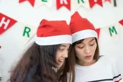 Two asia woman surprise when open gold gift box at holiday party. Two asia women surprise when open gold gift box at holiday party with decoration flag at stock image