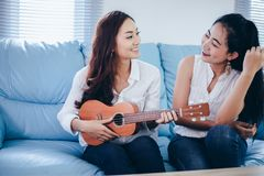 Two asia women are having fun playing ukulele and smiling at ho stock photo