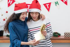 Two asia woman surprise when open gold gift box at holiday party. Two asia women surprise when open gold gift box at holiday party with decoration flag at Royalty Free Stock Photos