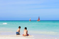Two Asian boys playing on the white sandy beach Royalty Free Stock Images