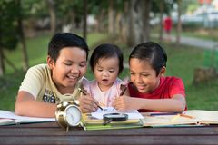 Two asian brothers playing with their little sister drawing together. Family concept Stock Photos
