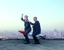 Two asian business man funny playing with rocket missile on buil Royalty Free Stock Image