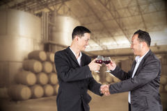 Two Asian business man holding a glass of wine and handshaking Stock Photos