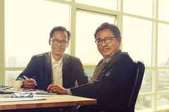 Two asian business man toothy smiling face in working office royalty free stock photography