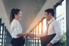 Two asian business people standing and shaking hands with together stock photo