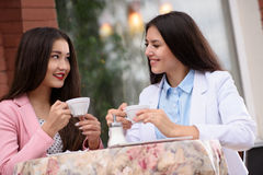 Two Asian business woman in outdoor cafe with Royalty Free Stock Images