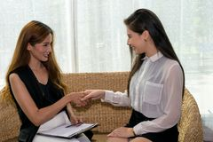 Two Business woman. Two Asian Business Woman Talking, Dealing and Signing Contract Royalty Free Stock Image