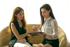 Two Business woman. Two Asian Business Woman Talking, Dealing and Signing Contract Royalty Free Stock Photos