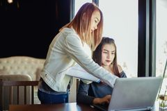 Two Asian business women using notebook working and Discussion o Royalty Free Stock Photos