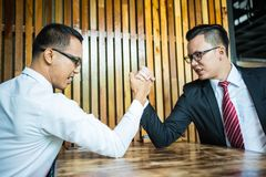 Two Asian businessman expressed a serious expression and fighting by used arm wrestling on wood table. royalty free stock photography