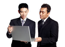 Two Asian Businessmen share business information. Portraits of two Asian Businessmen, Chinese and Malay, sharing business information on a laptop Royalty Free Stock Photos