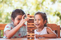 Two asian child girl playing wood blocks stack game together. With fun and happiness Royalty Free Stock Photography