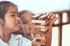 Two asian child girl playing wood blocks stack game. Together with fun and happiness Royalty Free Stock Photo