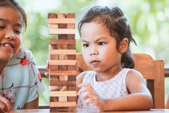 Two asian child girl playing wood blocks stack game. Together with fun and happiness Royalty Free Stock Photography