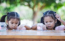 Two asian child girls counting and putting coin into bottle. Two asian little child girls counting and putting coin into glass bottle together in the garden. Kid royalty free stock photo
