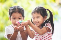 Two asian child girls catching candies falling from sky. Two asian child girls having fun to catching candies falling from the sky and share to each other stock photography