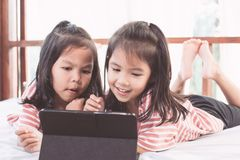 Two asian child girls having fun to play game in digital tablet. Two cute asian child girls having fun to play game in digital tablet together in the room in Royalty Free Stock Photos