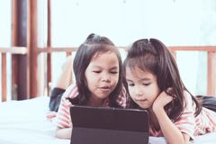 Two asian child girls having fun to play game in digital tablet Royalty Free Stock Image