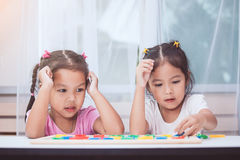 Two asian child girls having fun to play and learn magnetic alphabet Stock Photo