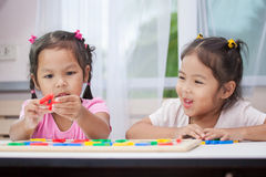 Two asian child girls having fun to play and learn magnetic alphabet Stock Photos
