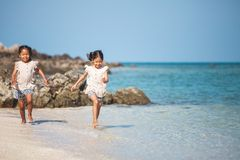 Two asian child girls having fun to play and run on beach together in summer vacation. Two cute asian child girls having fun to play and run on beach together in stock images