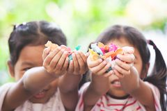 Two asian child girls holding sweet candies in thier hands. And share to each other stock photos
