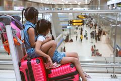 Two asian child girls sitting on suitcase waiting for boarding in the airport together. Two cute asian child girls sitting on suitcase waiting for boarding in royalty free stock photos