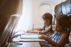 Two asian child girls traveling by an airplane and spending time by drawing and reading a book during the flight. Two cute asian child girls traveling by an royalty free stock image