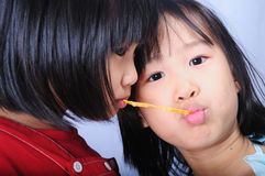 Two asian children eating fish snack together Royalty Free Stock Images