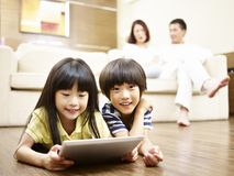 Asian children using digital tablet. Two asian children lying on floor playing video game using digital tablet while parents watching in the background royalty free stock photos