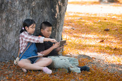 Two Asian children play tablet sitting in the garden. Two Asian children sitting in the garden summer time and tablet in hand with vintage tone,Education Stock Photo