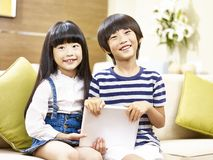 Two asian children sitting on couch looking at camera smiling. Two cute asian children little boy and little girl sitting on couch holding digital tablet looking stock photos