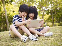 Two asian children using tablet outdoors. Little asian girl and boy sitting on grass using digital tablet outdoors in a park stock photo