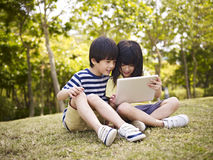 Two asian children using tablet outdoors. Little asian girl and boy sitting on grass using digital tablet outdoors in a park Royalty Free Stock Photos