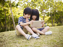 Two asian children using tablet outdoors. Little asian girl and boy sitting on grass using digital tablet outdoors in a park stock photography