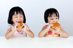 Two Asian Chinese little girl Eating Burger Royalty Free Stock Photos