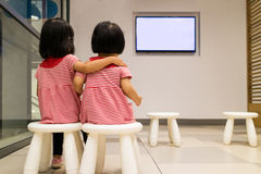 Two Asian Chinese Little Sister Watching TV. Indoor Royalty Free Stock Images