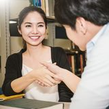 Two asian college students shaking hands in the library Royalty Free Stock Photos