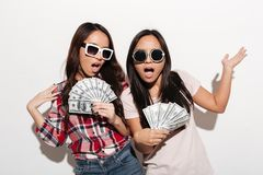 Two asian cool ladies sisters holding money. Photo of two asian cool ladies sisters wearing sunglasses standing isolated over white background. Looking camera Stock Photos