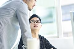 Two asian corporate executives discussing business in office. Two young asian businessmen having a discussion in front of computer in office stock photography