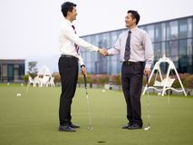 Two asian corporate executives shaking hands on golf course. Two asian corporate executives shaking hands after playing golf on rooftop court stock photos