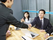 Asian business people shaking hands. Two asian corporate executives shaking hands during meeting in office royalty free stock images