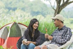 Two asian couple in nature camping. Asian Male and female look each other while baked barbecue in green nature Royalty Free Stock Photography
