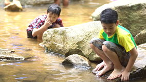 Two asian cute boy sit and play in the river . 4K ,Two asian cute boy sit and play in the river stock video