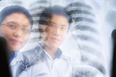 Two Asian doctor smiling through the xray result Royalty Free Stock Images