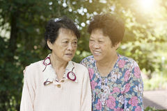 Two Asian elderly women. Candid shot of Asian elderly women talking at outdoor park in the morning stock photography