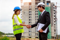 Two asian engineers shaking hands at construction site Stock Photography