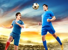 Two asian football player man jump in the air and duel heading the ball stock images